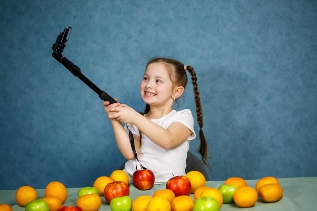 Маленькая девочка играет с фруктами и делает селфи по телефону. витамины и здоровое питание для детей.