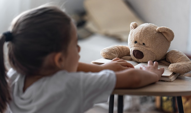 A little girl plays with her teddy bear and a book, teaches him to read, plays at school.