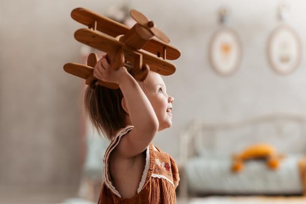 小さな女の子はおもちゃの木の飛行機で遊ぶ