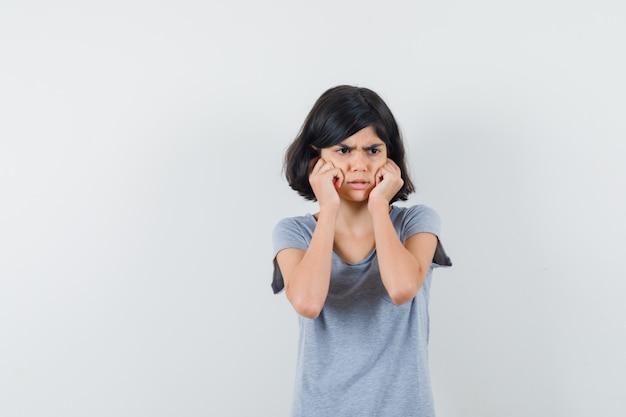 小さな女の子がtシャツに指で耳を差し込んで、怖がって、正面図を見てください。