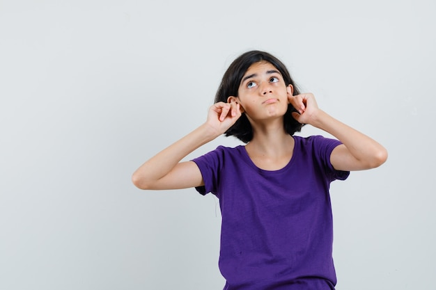 Little girl plugging ears with fingers in t-shirt and looking bored ,