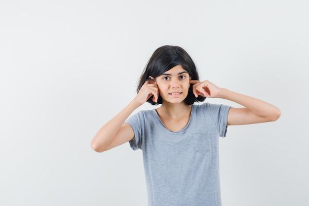 Bambina che collega le orecchie con le dita in maglietta e sembra confuso, vista frontale.