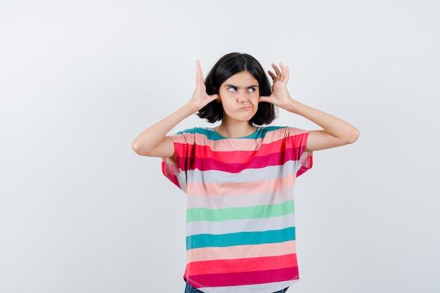 Bambina che tappa le orecchie con i pollici, distoglie lo sguardo in maglietta e sembra dispiaciuta. vista frontale.