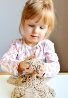 Little girl plyaying with kinetic sand at home