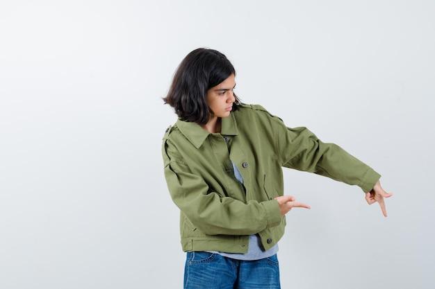 Маленькая девочка указывая в сторону в пальто, футболке, джинсах и выглядит уверенно, вид спереди.
