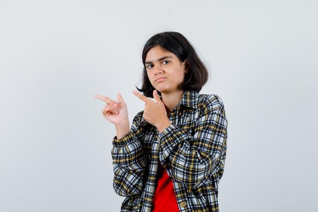 셔츠, 재킷을 옆으로 가리키는 어린 소녀와 불쾌한 찾고. 전면보기.