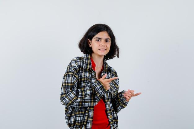 셔츠, 재킷 전면 보기를 제쳐두고 가리키는 어린 소녀.