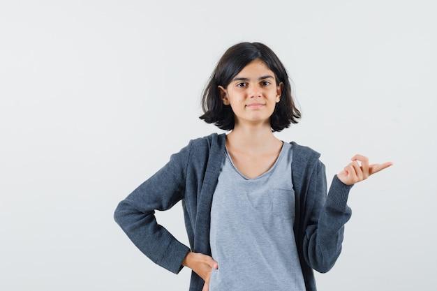 Tシャツ、ジャケットを脇に向け、自信を持って見える少女。