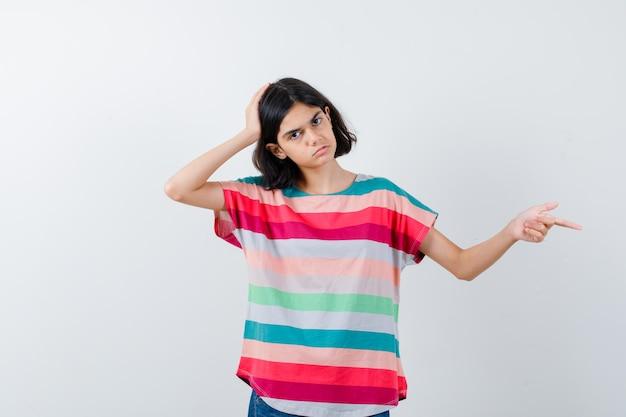 Маленькая девочка указывая в сторону, держась за голову в футболке и грустно, вид спереди.