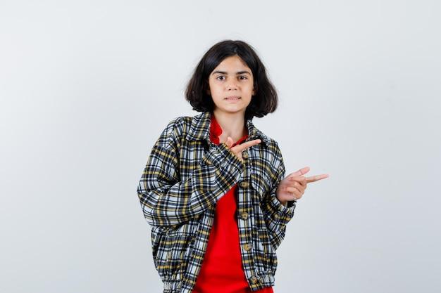 Bambina che indica da parte in camicia, vista frontale della giacca.