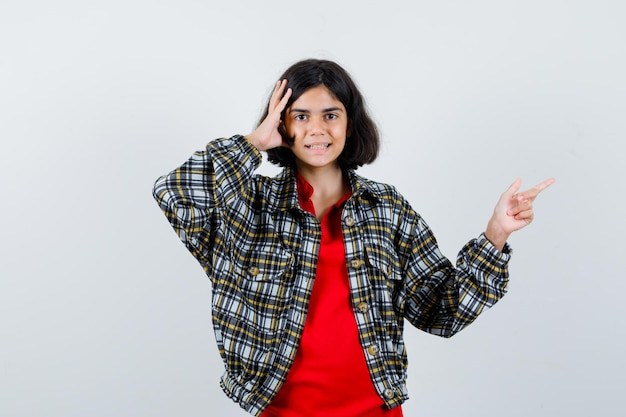 Little girl pointing aside while holding hand on head in shirt,jacket and looking talkative , front view.
