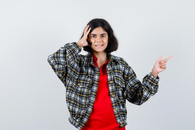 어린 소녀가 셔츠, 재킷을 입은 머리에 손을 잡고 수다스러운 앞모습을 바라보면서 옆으로 가리키고 있습니다.