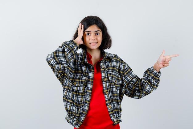 Маленькая девочка указывая в сторону, глядя на камеру в рубашке, куртке и глядя сфокусированно. передний план.