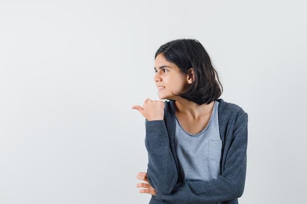 Tシャツ、ジャケット、夢のように見える親指で脇を指している少女。正面図。