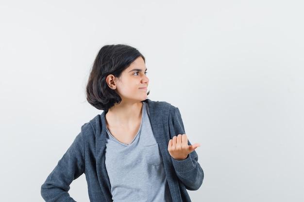 Tシャツ、ジャケット、陽気に見える、正面図で親指で脇を指している少女。