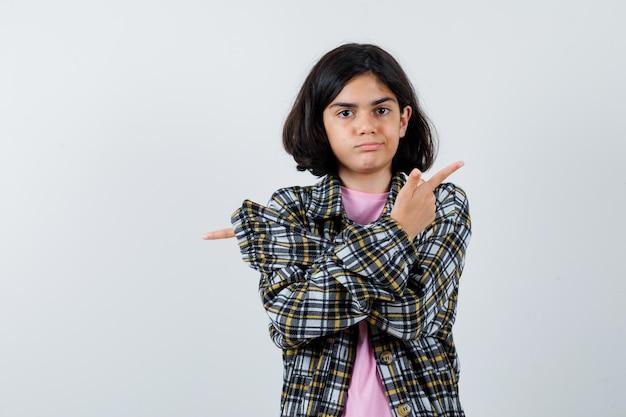 셔츠, 재킷의 다른 면을 가리키고 혼란스러워 보이는 어린 소녀, 전면 보기.
