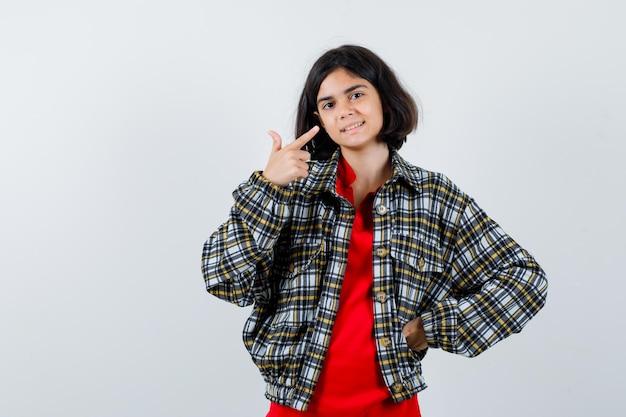 셔츠, 재킷을 입은 그녀의 미소를 가리키며 기뻐하는 어린 소녀. 전면보기.