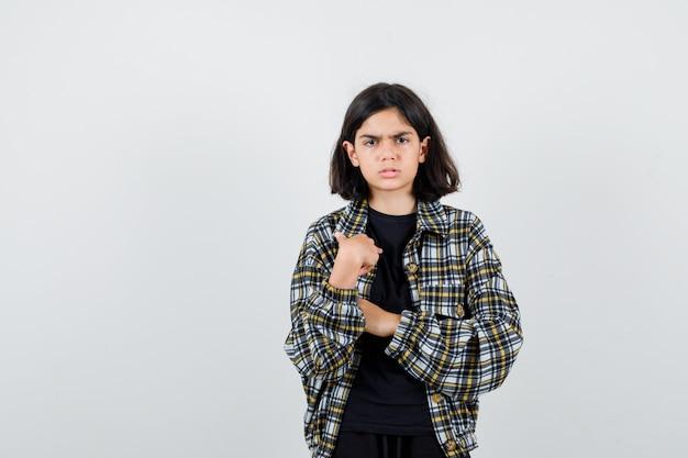 Маленькая девочка, указывая на себя в футболке, куртке и нерешительно глядя, вид спереди.