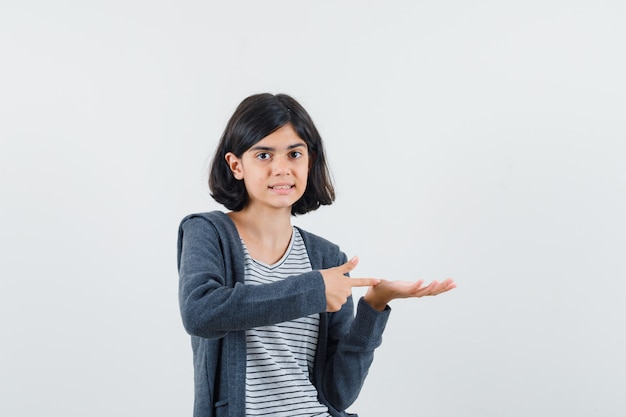 Tシャツ、ジャケットに抱かれているふりをして自信を持って見える何かを指している少女