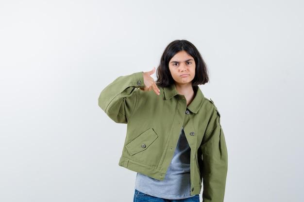 Bambina che indica giù in cappotto, maglietta, jeans e sembra sicura. vista frontale.