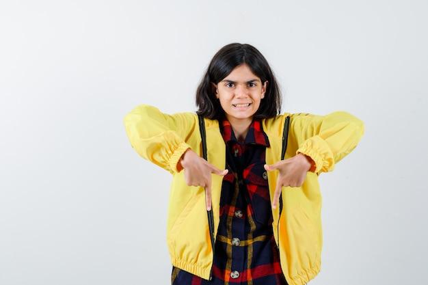 チェックのシャツ、ジャケットで下向きで幸せそうに見える少女
