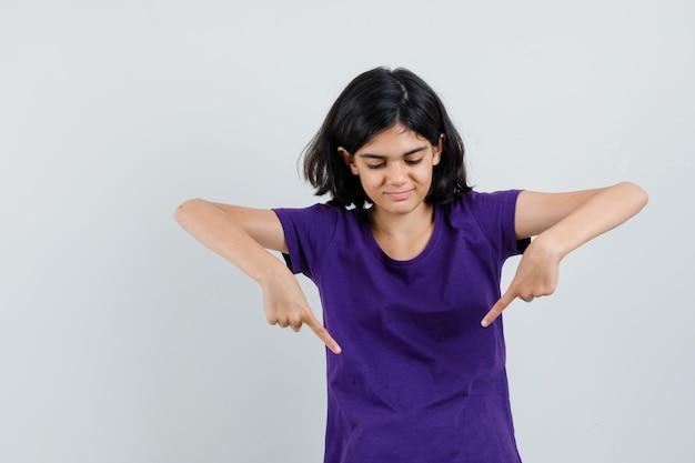 Bambina con la punta rivolta verso il basso in maglietta e guardando allegra.