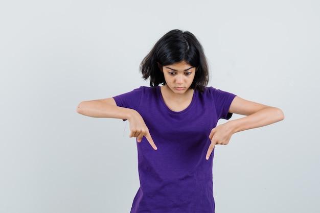 Bambina con la punta rivolta verso il basso in maglietta e guardando scioccato.