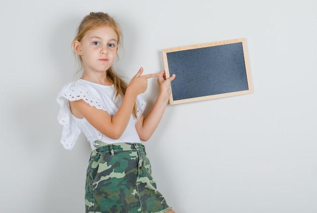 어린 소녀 흰색 t- 셔츠, 치마에 칠판에 손가락을 가리키는 자신감을 찾고.