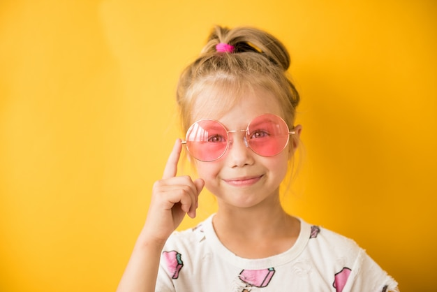 Little girl pointing finger at pink glasses on yellow
