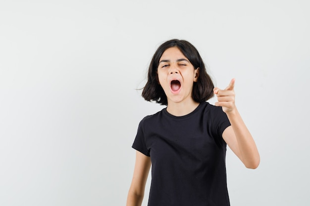 Little girl pointing at front while yawning in black t-shirt front view.