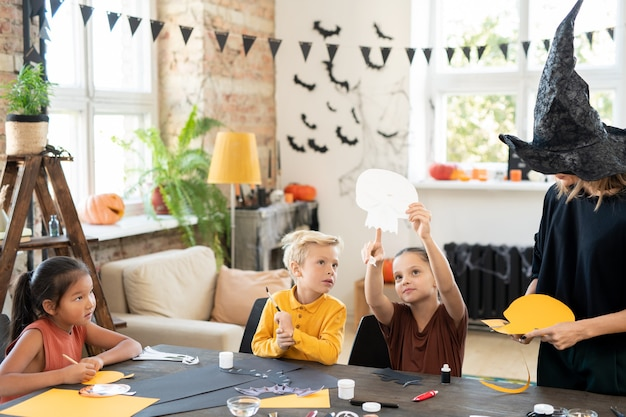 Little girl pointing at halloween paper symbol while showing it to cute boy