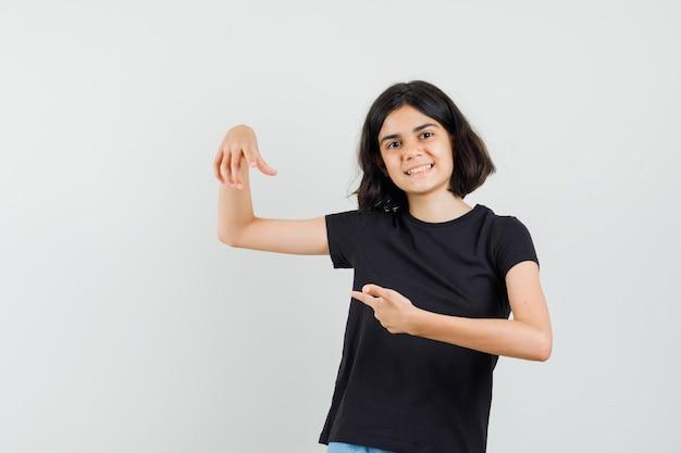 Bambina che punta il dito verso il basso in maglietta nera e guardando allegro, vista frontale.