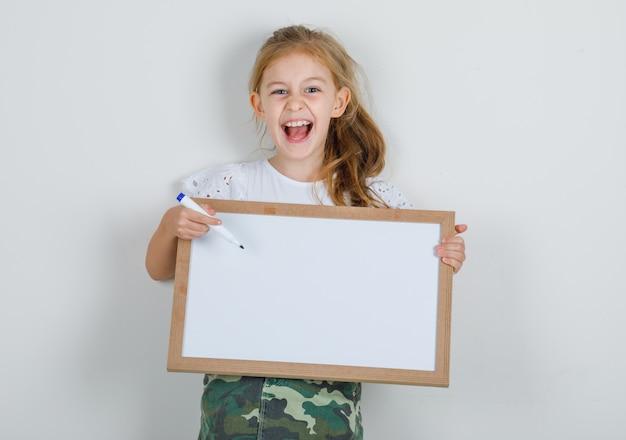 Bambina che indica il pennarello a bordo bianco in maglietta bianca