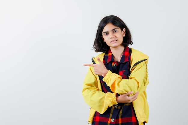 チェックのシャツ、ジャケットで左側を指して自信を持って見える少女。正面図。