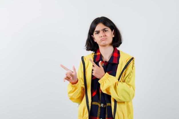 チェックのシャツ、ジャケットで左側を指して自信を持って見える少女