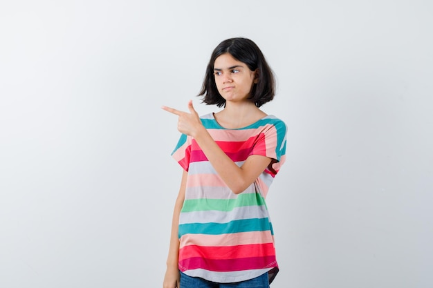 Tシャツの左側を指して、焦点を合わせているように見える少女。正面図。