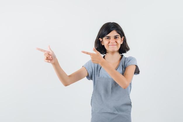 Tシャツ、エプロンで左側を指して陽気に見える少女。正面図。