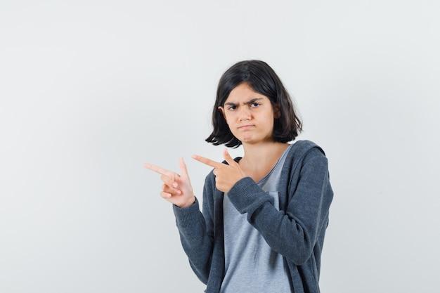 Tシャツ、ジャケットで左側を指して物思いにふける少女