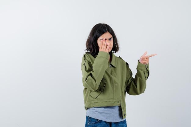 小さな女の子が右側を指して、コート、tシャツ、ジーンズで手を覆い、自信を持って、正面図を探しています。