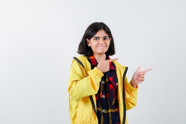 チェックのシャツ、ジャケットで右側を指して自信を持って見える少女