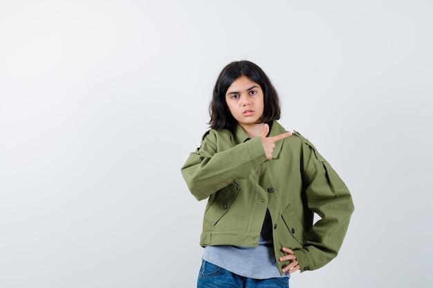 コート、tシャツ、ジーンズで右側を指して自信を持って見える少女。正面図。