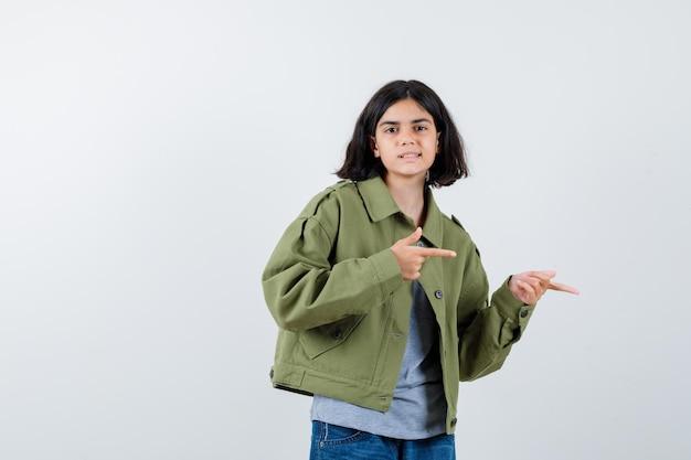 코트, 티셔츠, 청바지를 입고 오른쪽을 가리키고 자신감을 보이는 어린 소녀. 전면보기.