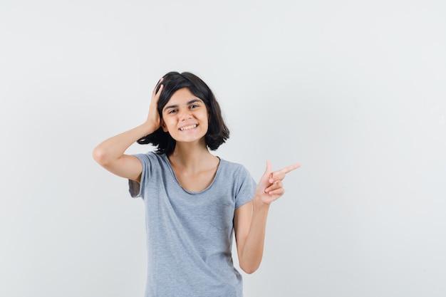 Tシャツで右側を指して元気そうな女の子。正面図。