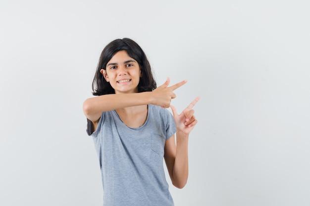 Tシャツで右側を指して陽気に見える少女、正面図。