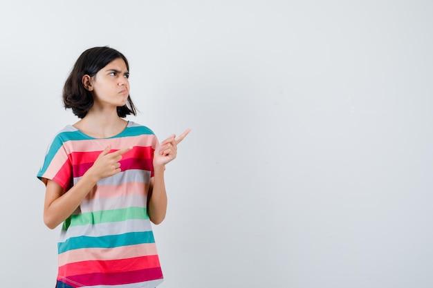 Tシャツで右側を指して物思いにふける少女。正面図。