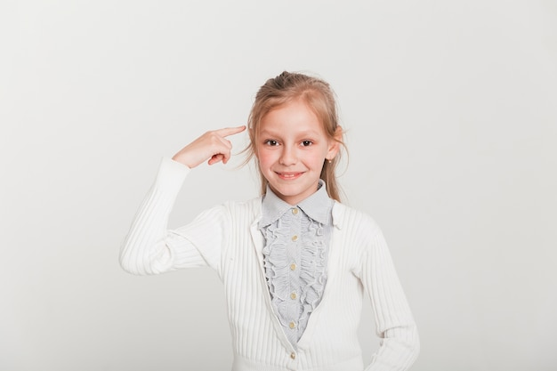 Little girl pointing towards head