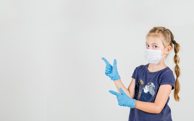 Little girl pointing two fingers looking at camera in t-shirt, gloves and mask front view.