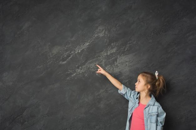 灰色のスタジオの背景を指している少女。幸せなカジュアルな子供が身振りで示して楽しんでいます。成功と目標達成の概念、コピースペース