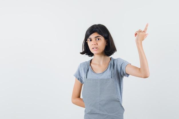 Tシャツ、エプロンで上向きで困惑している少女。正面図。
