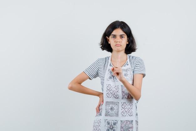 Bambina che indica in su in maglietta, grembiule e che sembra seria